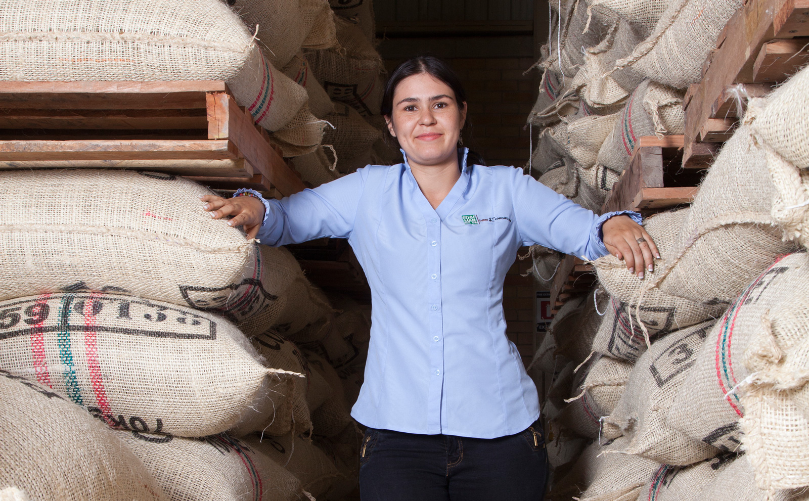 ED&F Man Coffee - worker standing among coffee sacks